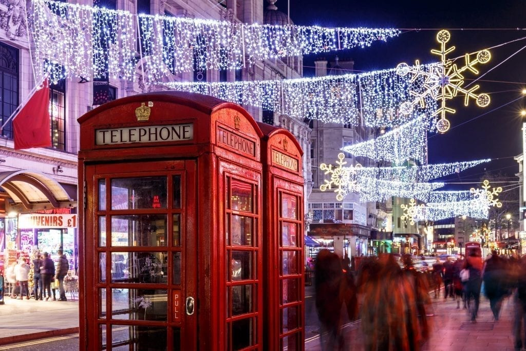 Classic red telephone booths in London with Christmas lights hanging above them and shoppers walking by