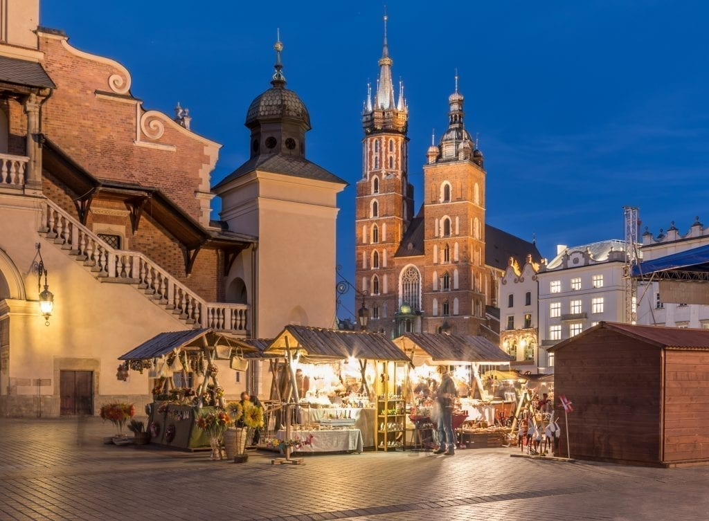 Main square of Krakow Poland at blue hour with a Christmas market open in the foreground