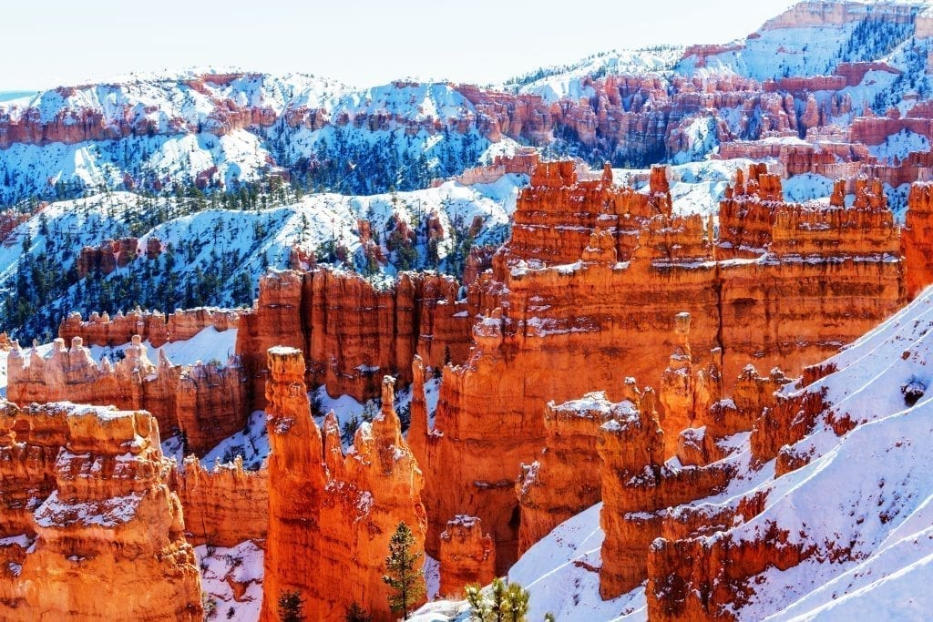 View of Bryce Canyon amphitheater in winter with snow on the ground surrouding the hoodoos