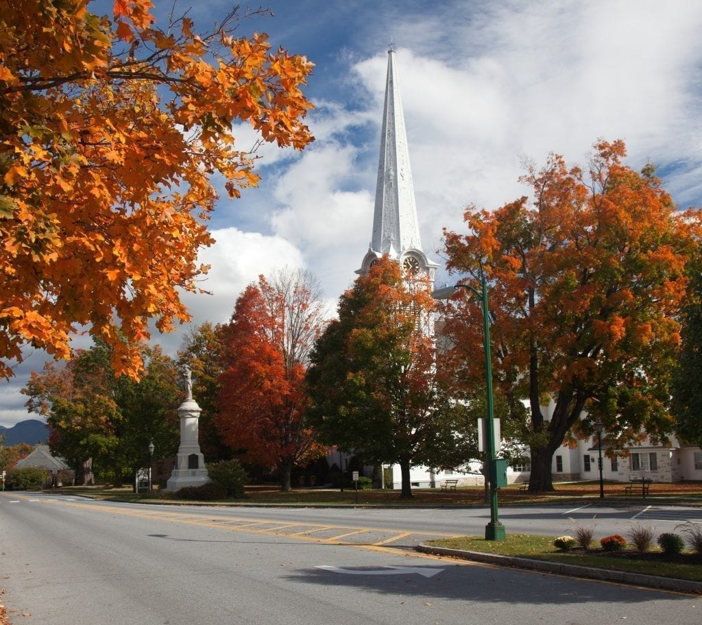 Fall foliage along a small street in Manchester Vermonth with a white church visible in the background