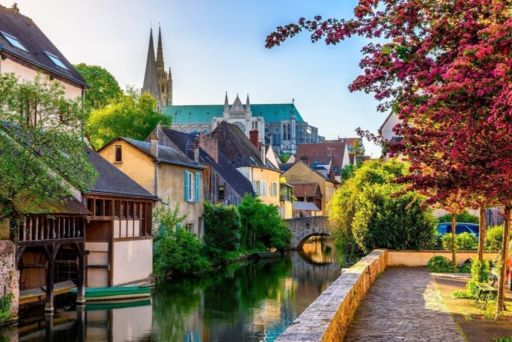Small canal in Chartres France with half-timbered houses lining one side. Chartres is a fun Paris day trip destination