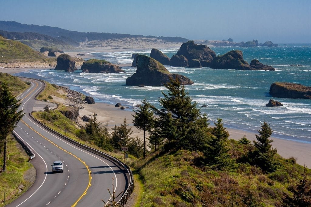 One car driving along the oregon coast as shot from above