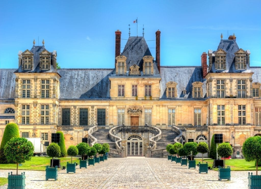 Exterior of Château de Fontainebleau as seen from the front, one of the best day trips from Paris France