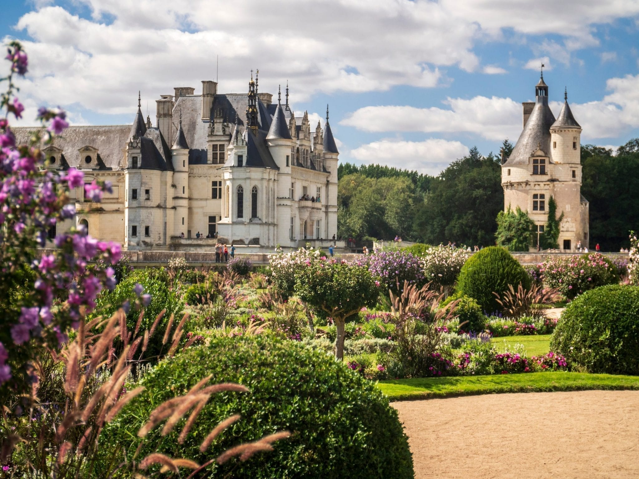 Château Chenonceau as seen from across the garden with pink flowers in the foreground. Château Chenonceau is one of the best day trips from paris france