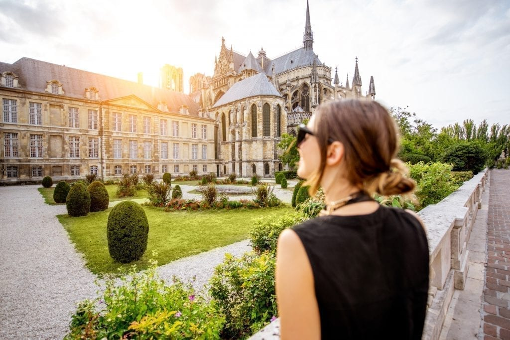 Young woman in a black tank top and sunglasses standing in front of the Reims cathedral