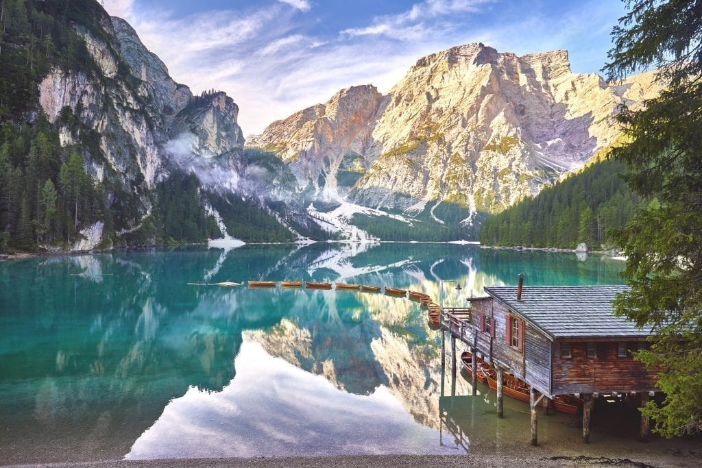 Lago di Braies in the early morning with a line of boats tied to the dock at the boathouse. Lago di braies is at the top of any list of italy beautiful places
