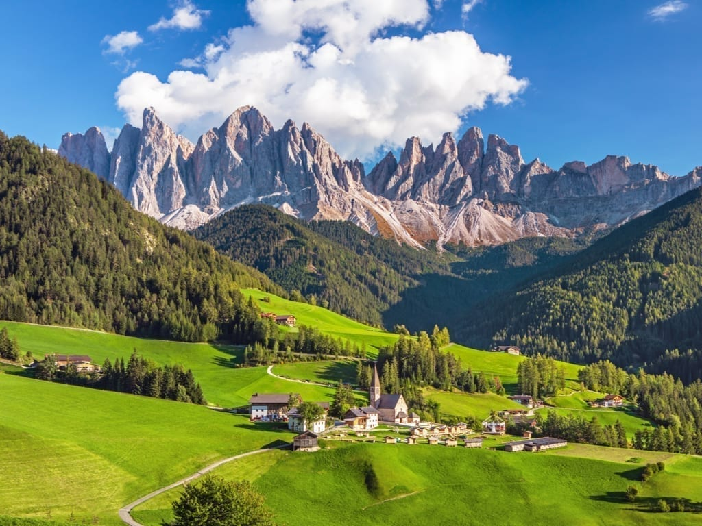 View of the Italian Dolomites on a clear day with a village visible below it.