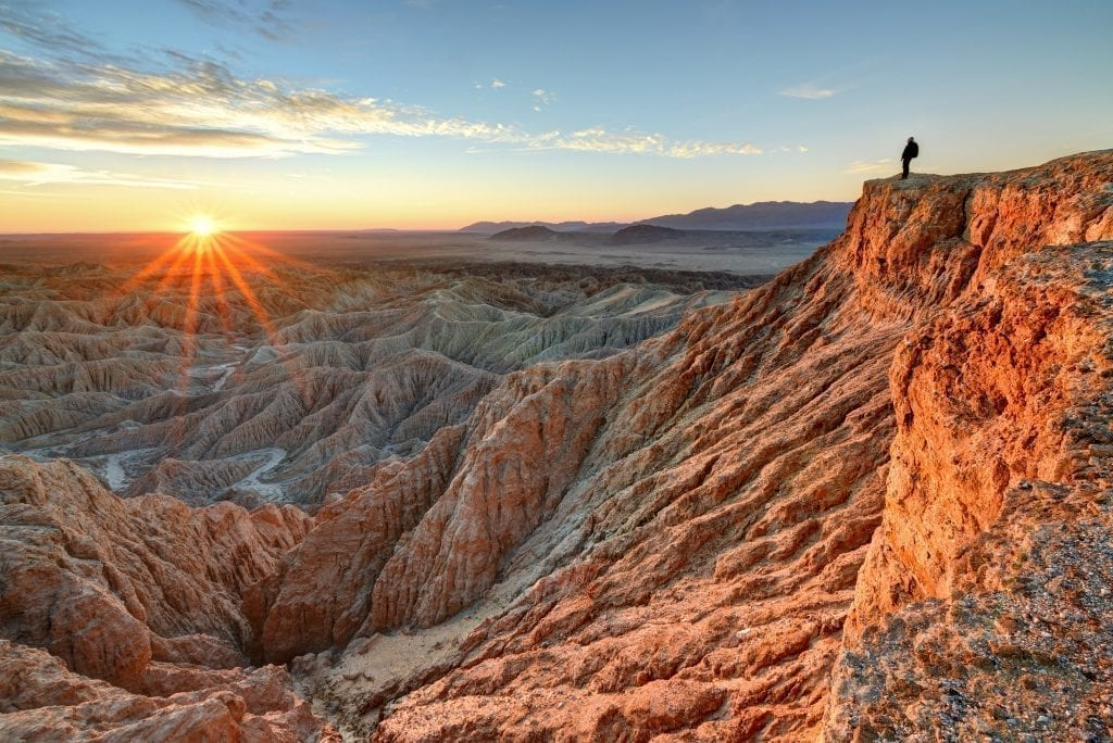 Hiker overlooking a sunrise in Anza Borrego State Park southern California, one of the best stops on a southern california road trip itinerary