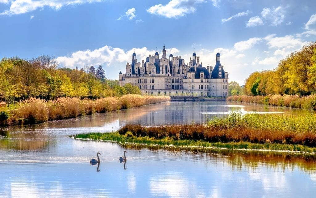Château de Chambord as seen from a distance with a pond in the foreground that has 2 swans on it