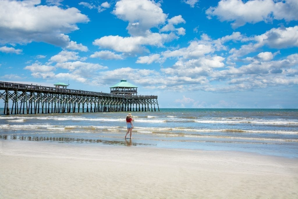 Woman walking along the water next to the pier at Folly Beach on a partly cloudy day. Folly Beach is a fun place to visit during a weekend in charleston sc