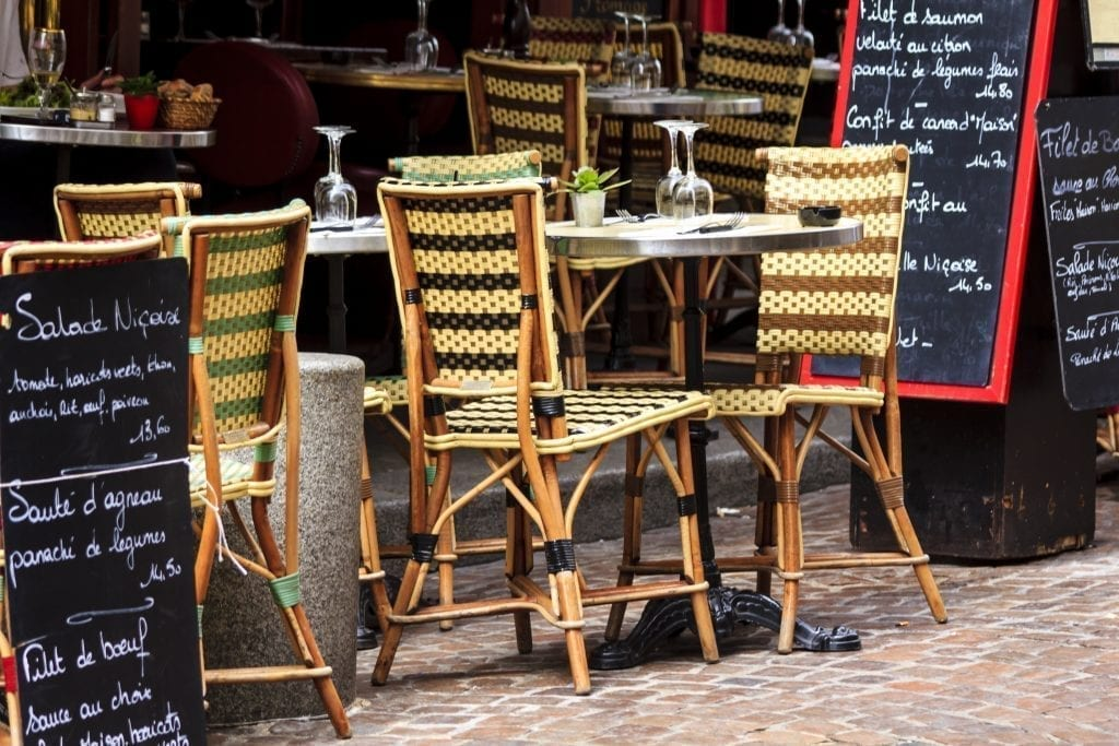 Sidewalk table at a small restaurant in Paris with 2 chairs visible and menu boards to the side