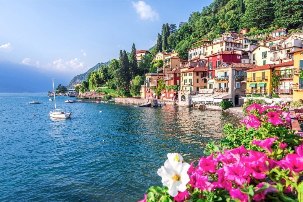 lake como with a sailboat on it with the village of varenna visible to the right side of the photo