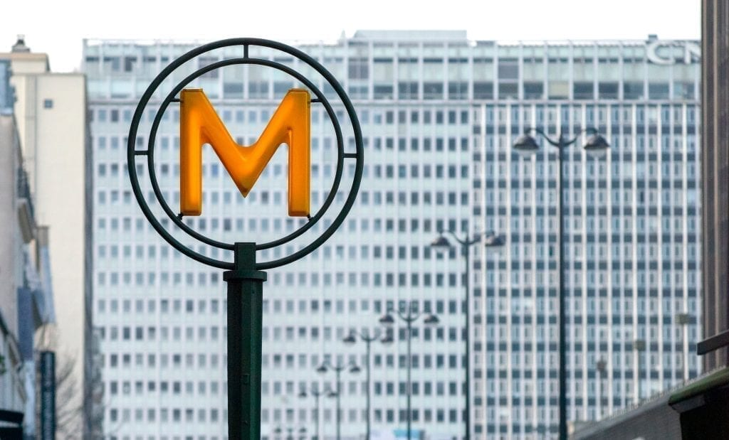 "Yellow ""M"" sign denoting the Montparnasse-Bienvenüe metro station in Paris France"