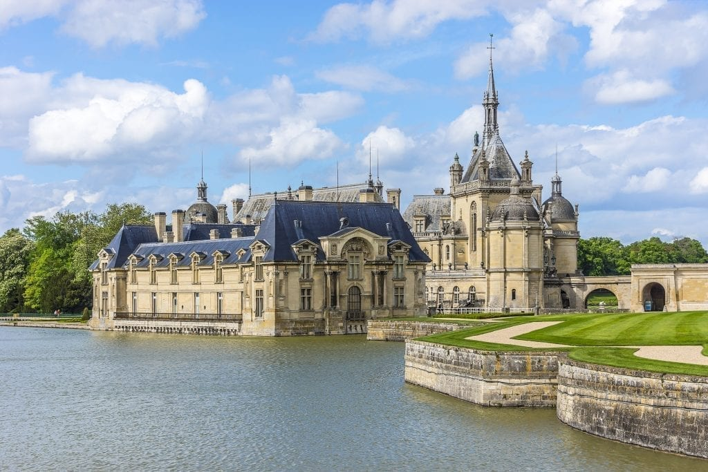 Exterior of Chateau de Chantilly as seen from across the pond, one of the best paris day trips