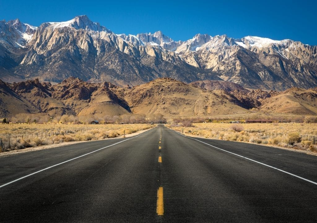 view of mount whitney with an empty road in the foreground. mount whitney is a fantastic addition to a usa west coast road trip route