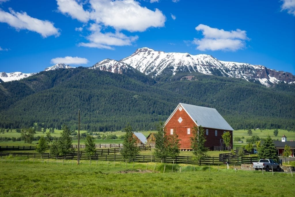 Wallowa mountains in northeastern Oregon with a red barn in the foreground. northeast oregon is an offbeat usa west coast road trip itinerary