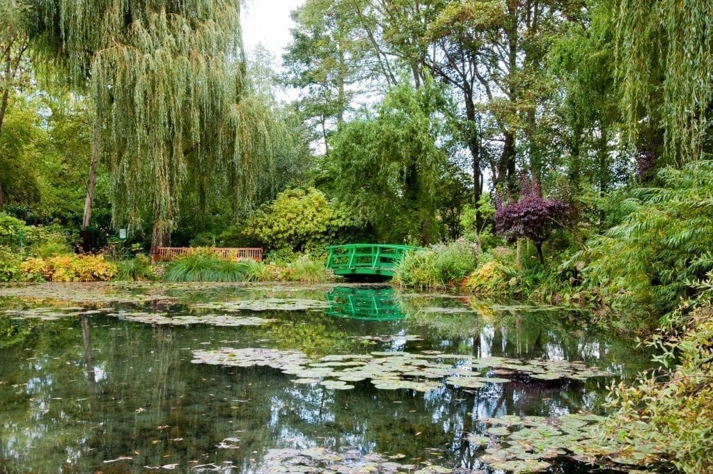 Water gardens of Giverny with green bridge visible in the center back. Giverny is one of the most fun day trips from Paris France
