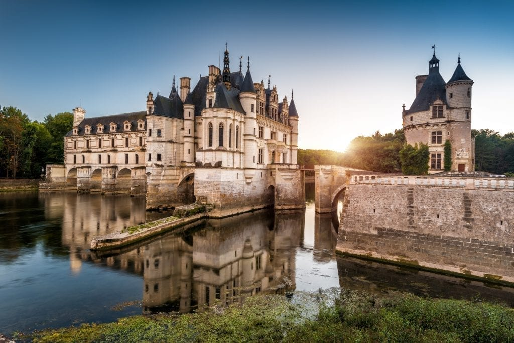 ChâteauChenonceau as seen from the side at sunset with water in the foreground. This chateau is one of the best day trips from Paris France!