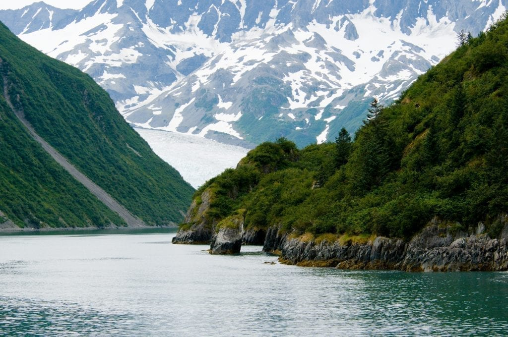 fjord in alaska with a glacier visible in the background of the image. alaska is an incredible place for west coast usa road trip ideas