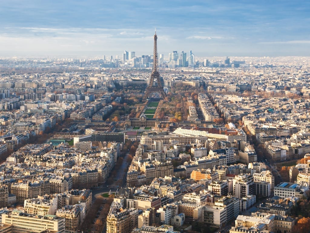 View from Montparnasse Tower Paris with the Eiffel Tower in the center of the photo and La Defense visible behind it