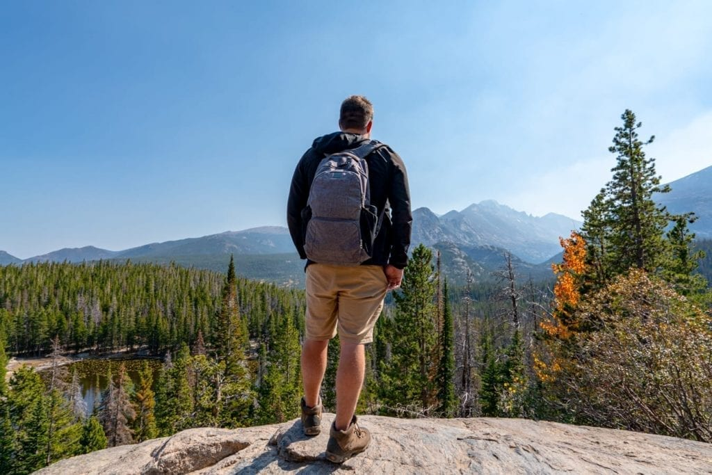 jeremy storm in a gray backpack hiking in rocky mountain national park