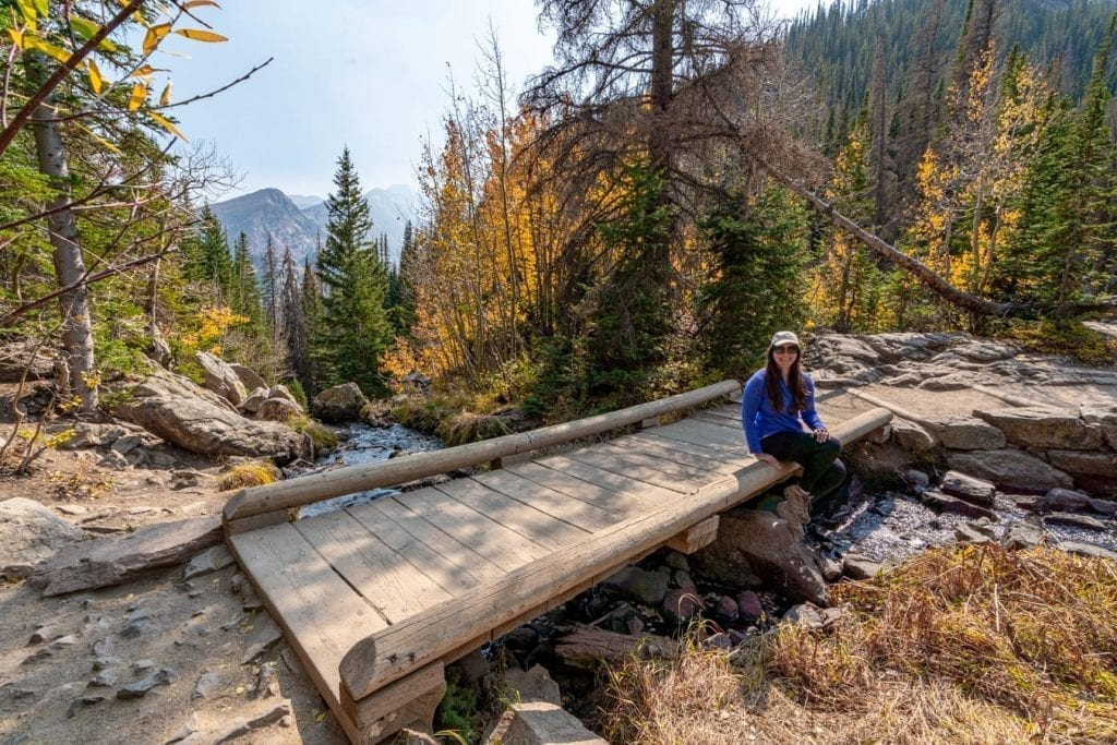 Kate Storm sitting on a wooden bridge during a hike in Rocky Mountain National Park