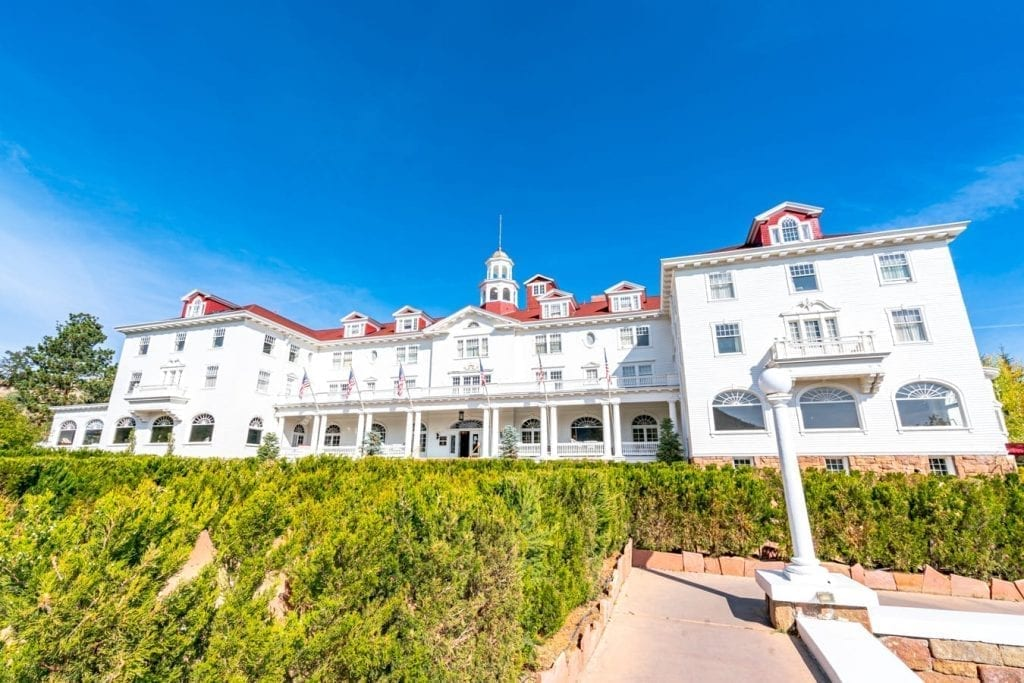 the front facade of the stanley hotel in estes park co with hedges visible in the foreground
