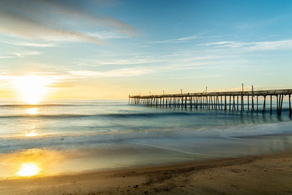 fishing pier at sunrise in rodanthe, one of the best travel destinations in north carolina for couples