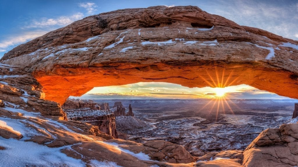 sunrise at mesa arch in canyonlands np with a sun flare and some snow on the ground