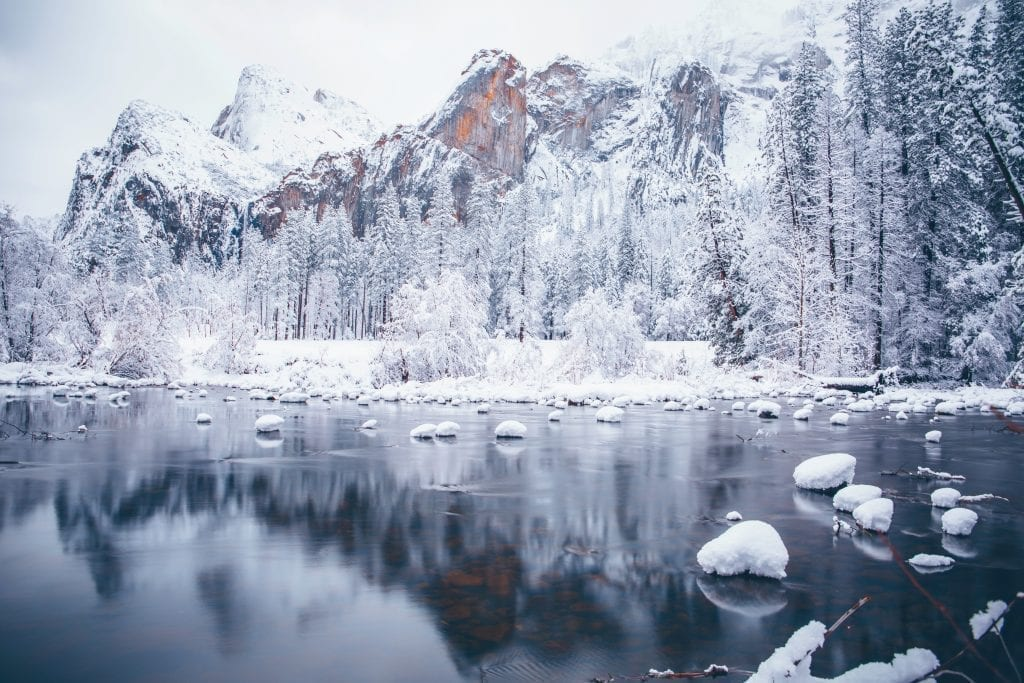lake in yosemite national park in winter with snow covering the trees and ice on the lake