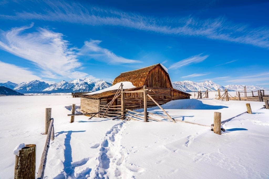 19th century barn on Mormon Row in Grand Teton National Park covered in snow. Grand Teton is one of the best national parks to visit in january december february