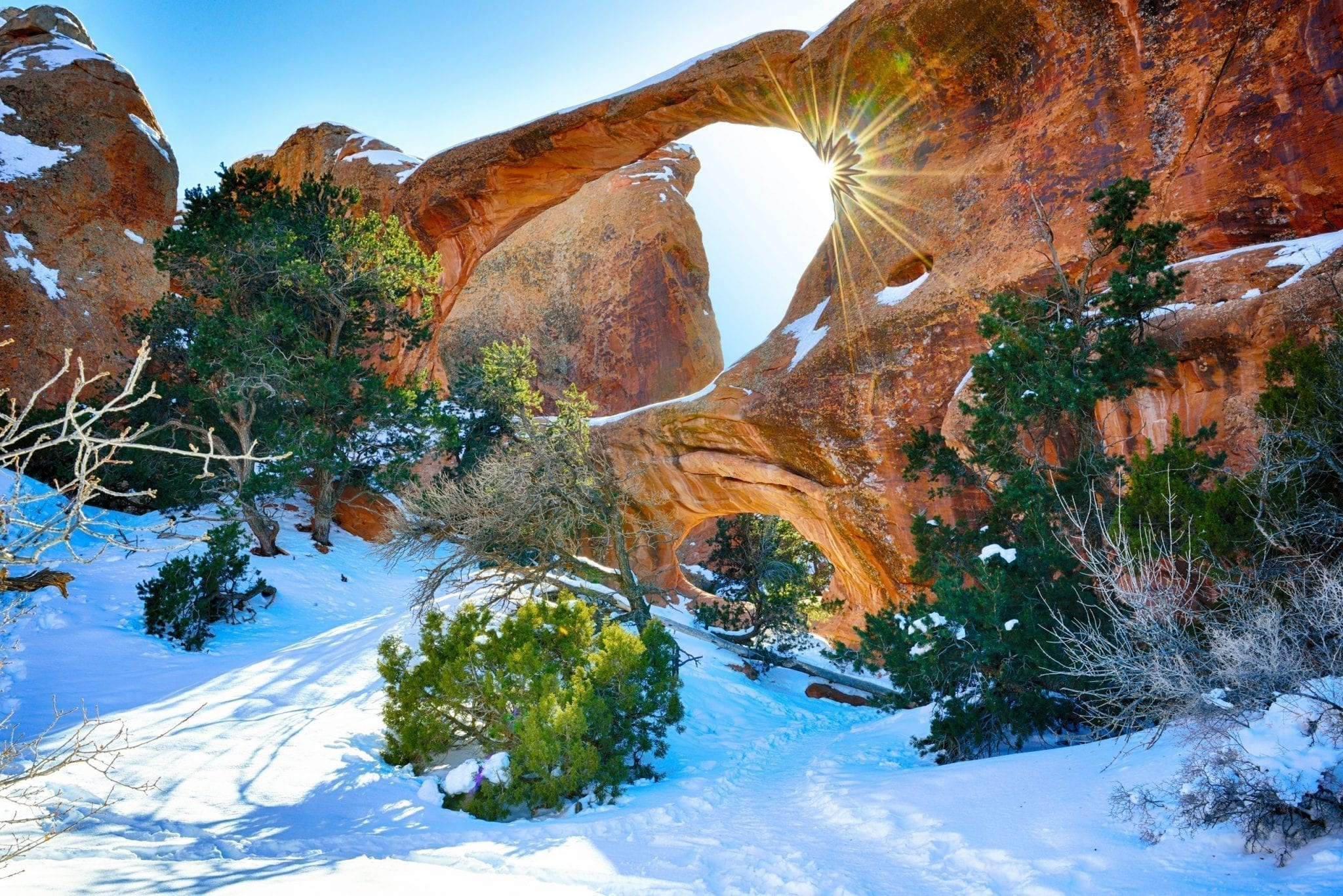 Arch in Arches NP with a sun flare and snow on the ground. arches in winter usa national parks to visit