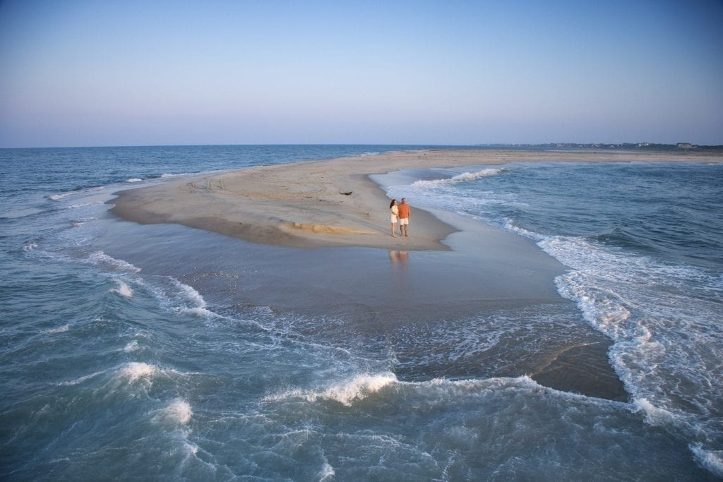 couple standing on a sand bar on bald head island, one of the most romantic getaways in nc