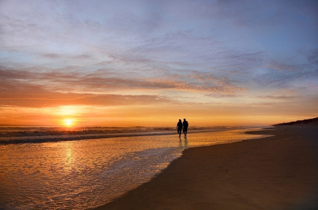 couple walking along the beach at sunset in the outer banks, one of the most romantic getaways in north carolina for couples