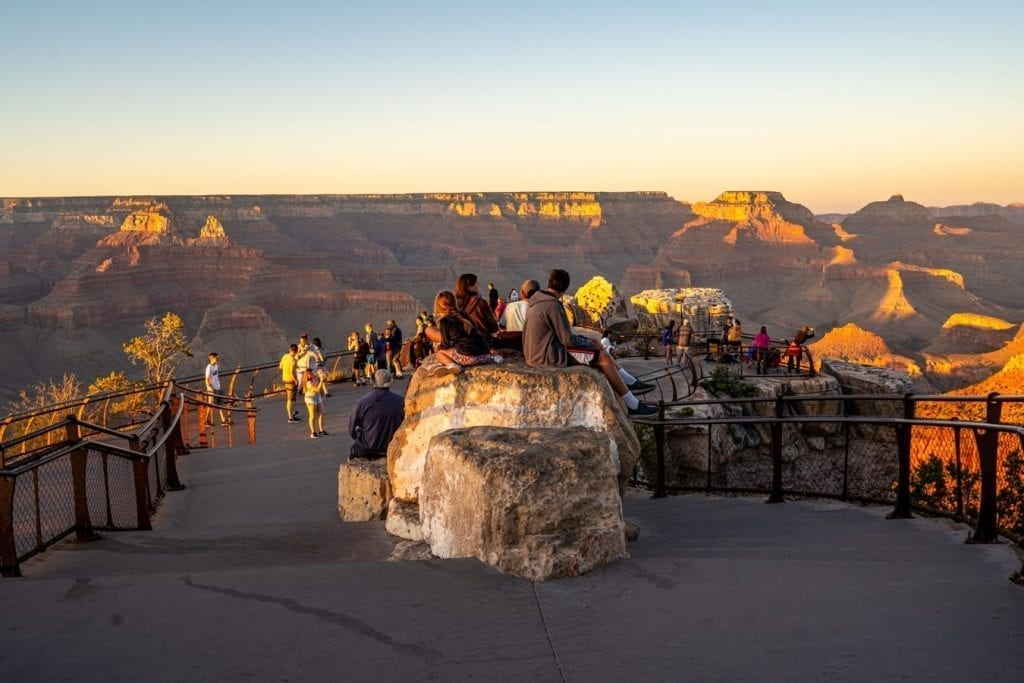a crowd of people watching the sunset at mather point near grand canyon rim trail