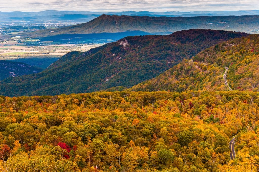 view of shenandoah national park from above during fall foliage season. a small section of skyline drive is visible on the right