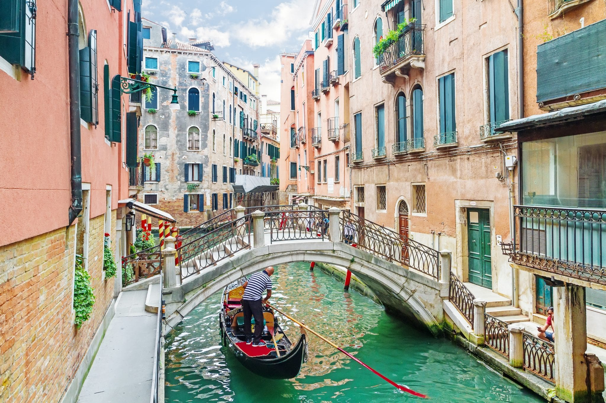 venetian canal with a gondola passing under a bridge. one of the fun facts about venice italy is that there are far fewer gondolas now than in the past