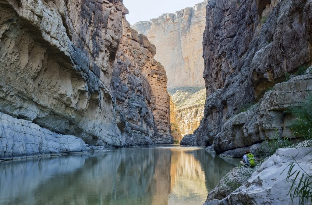 hiker sitting in santa elena canyon in big bend np, one of the most underrated usa national parks