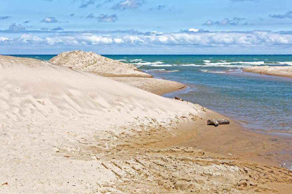 white sand beach at indiana dunes with bright blue water on the right