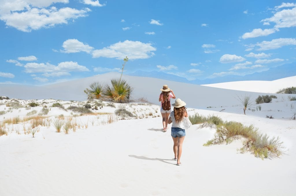 two young women hiking over sand dunes in white sands national park, one of the most beautiful national parks in america