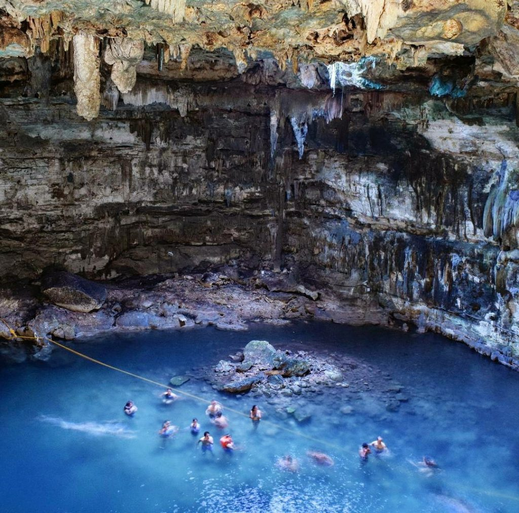 cenote samula as seen from above with a handful of swimmers enjoying the cenote