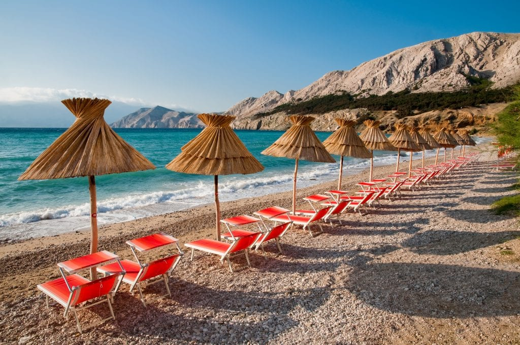 small beach on krk island with straw sunshades and red beach chairs