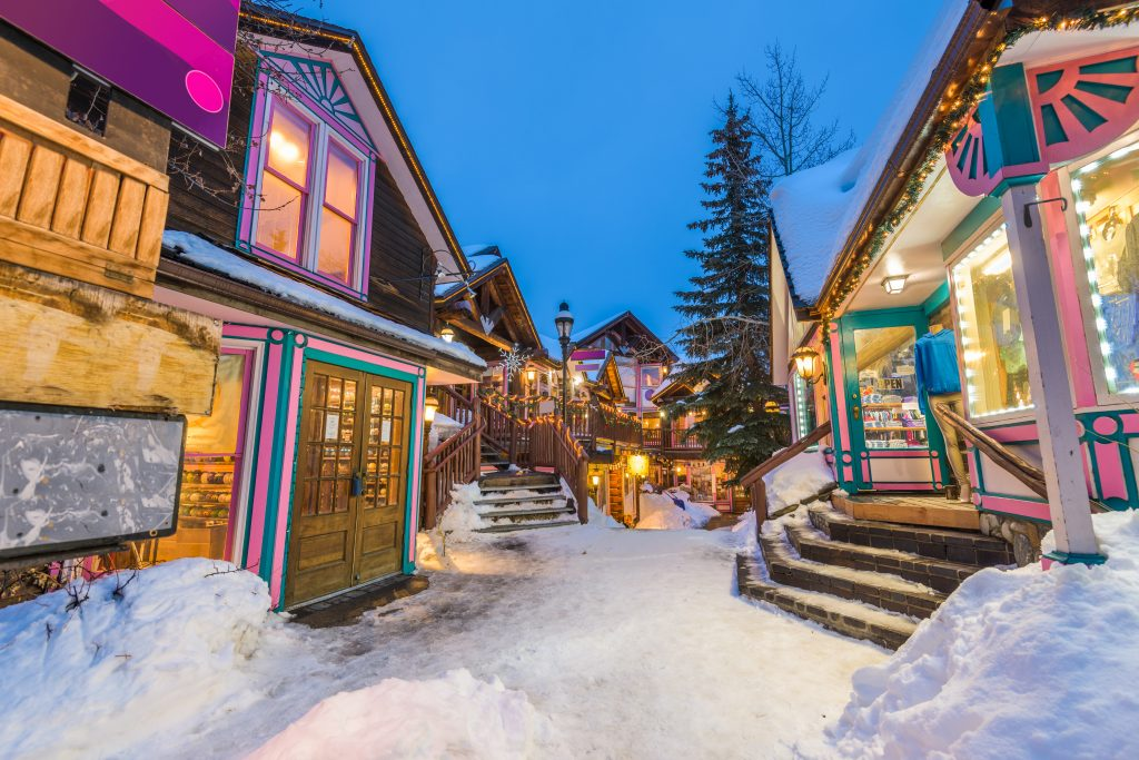 small street in breckenridge in winter, with snow on the ground and christmas lights up