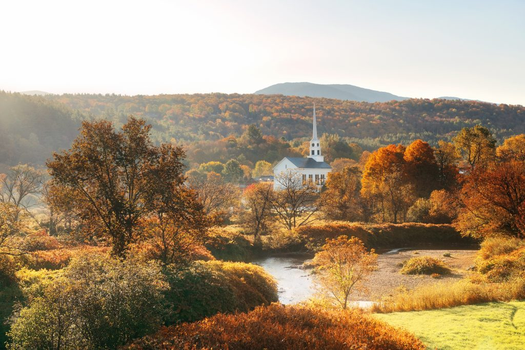 white church in stowe vermont in the fall, surrounded by fall foliage