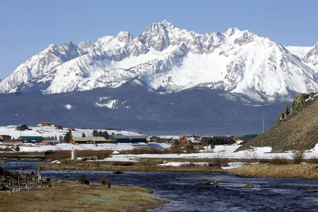 stanley idaho as seen from across a river, dwarfed by a snowcapped mountain in the background
