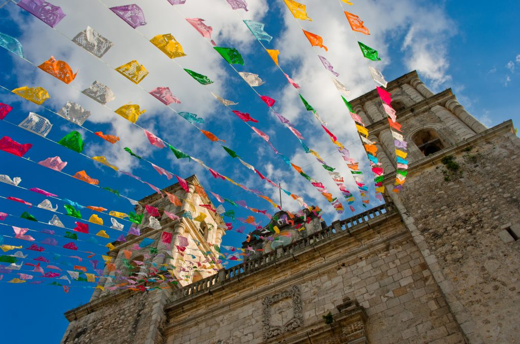 colorful flags on iglesia de san servacio, one of the most fun things to do in valladolid mexico