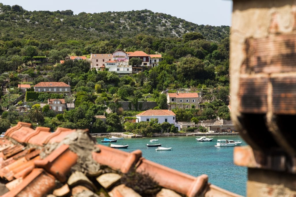 harbor of kolocep croatia as seen across red tiled rooftops