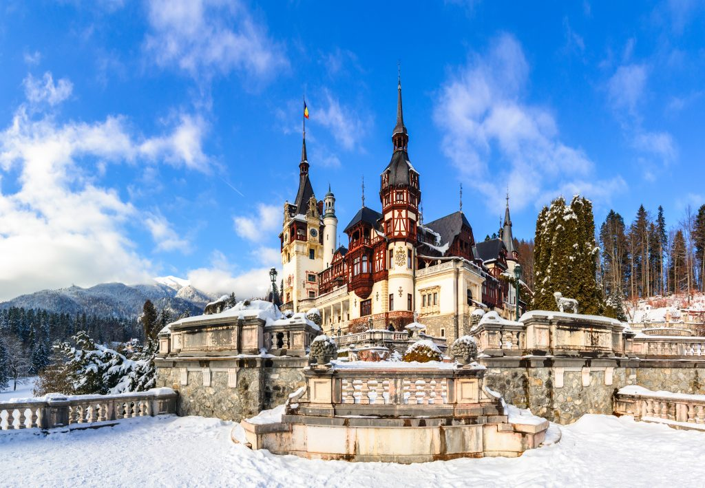 peles castle romania in winter after a snowfall, one of the best bucket list europe travel destinations