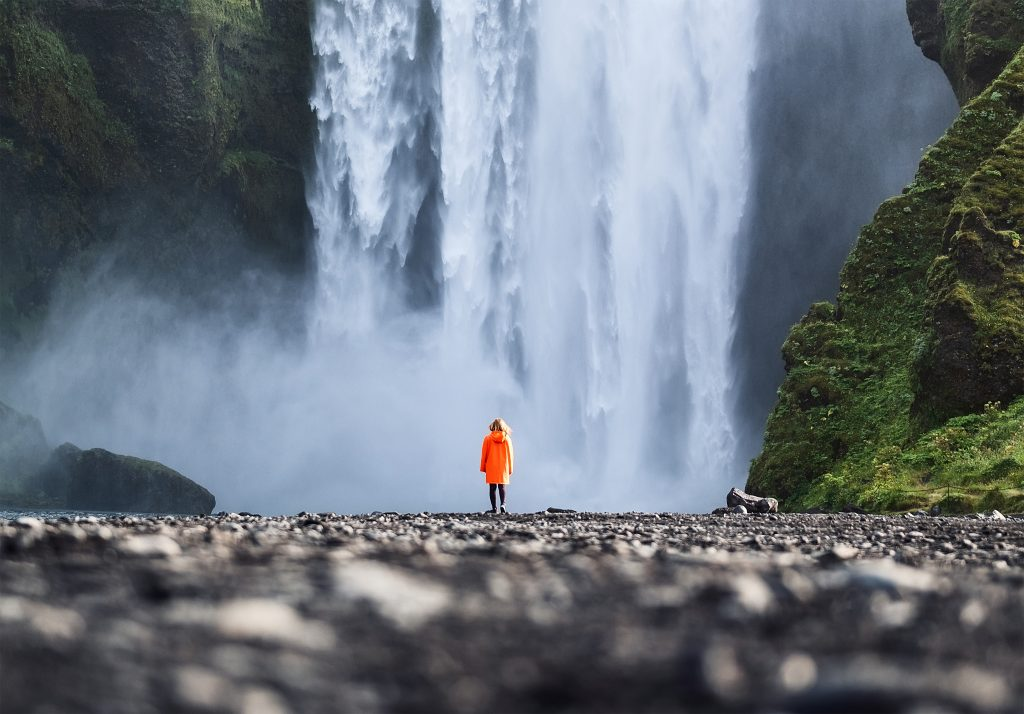 woman in an orange raincoat standing in front of skogafoss waterfall in iceland, one of the best tourist attractions in europe