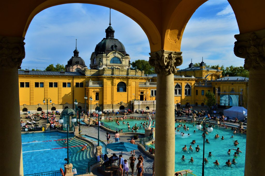 view of Szechenyi Thermal Baths from under an arch in budapest hungary